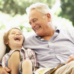 Grandfather With Grandson Reading Together On Sofa Laughing