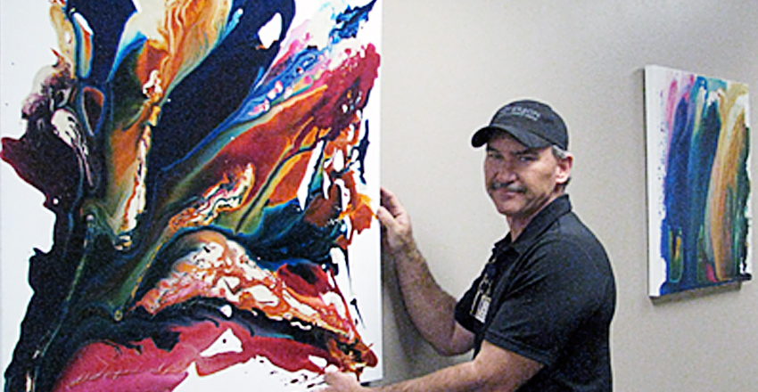 workman hanging art in gallery